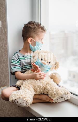un petit garçon dans un masque est assis à la maison en quarantaine et regarde la fenêtre dans un endroit avec un ours en peluche. Prévention du coronavirus et du Covid - 19. Con