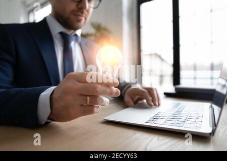 Homme d'affaires tient l'ampoule sur l'ordinateur
