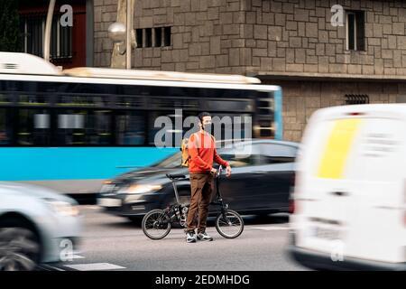 Photo de l'homme portant un masque de visage à vélo dans la ville.