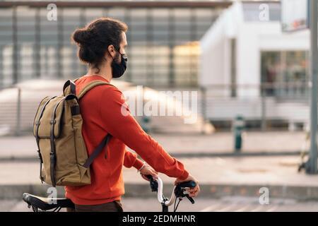 Photo de l'homme portant un masque de visage attendant dans un zébré croisant avec son vélo amovible.