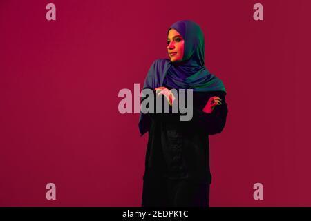 Jeune. Belle femme arabe dans hijab élégant isolé sur fond bordeaux studio dans la lumière néon avec espace de copie pour la publicité. Mode, beauté, style concept. Modèle féminin avec maquillage tendance, accessoires.