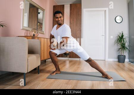 Vue de face d'un homme afro-américain souriant qui fait une fente latérale exercice à la maison