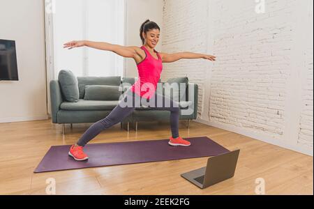 Jeune femme latine belle s'entraîner à la maison connectée à un cours de fitness en ligne sur l'ordinateur portable. Femme entraîneur personnel sur zoom teachin