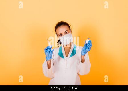 Femme médecin afro-américaine, masque, stethoskope, vaccin de robe en studio