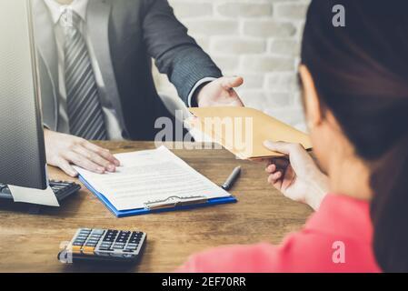 Homme d'affaires recevant l'enveloppe (argent) d'une femme tout en faisant le contrat - concept de corruption