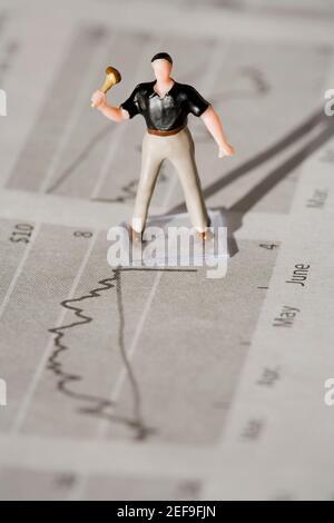 Figurine d'un travailleur manuel dans un journal financier