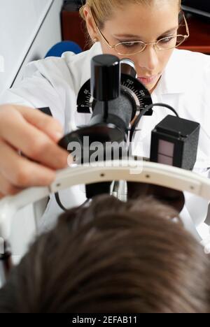 Gros plan d'une optométriste féminine examinant les yeux d'un patient