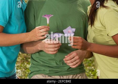 Vue en coupe centrale de trois amis tenant des fleurs