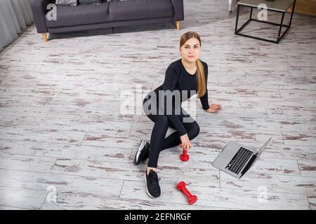 Jeune femme belle entraîneur dans un haut noir et leggings est assis avec un ordinateur portable et des montres en ligne d'entraînement, de la forme physique à la maison pendant la quarantaine. Li sain