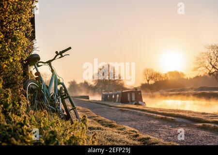Bateau sur le canal avec VTT à gauche contre la haie lever du soleil tôt le matin à l'aube avec lumière dorée dans le ciel La rivière Trent et la brume se levant