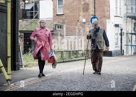 Un couple plus âgé se promenant dans une rue pavée portant des masques Covid 19, Margate, Kent.
