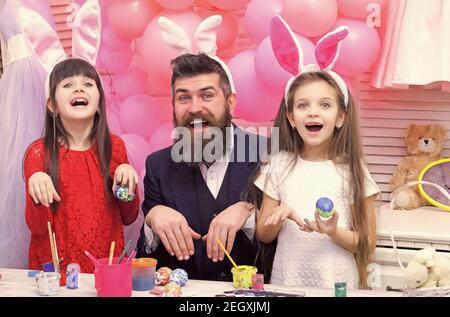Le père et les filles peignent des œufs. Une famille heureuse se prépare pour Pâques. Les petites filles adorables portent des oreilles de lapin. Banque D'Images