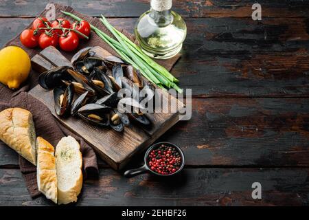 Moules cuites dans la sauce à l'ail avec le persil et l'ingrédient, sur la planche à découper en bois, sur le fond de la table en bois foncé, avec l'espace d'imitation et l'espace FO