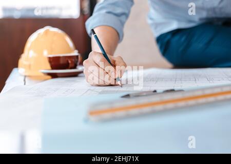 les ingénieurs tenant un stylo pointant vers un bâtiment et dessinant un plan de construction de dépenses comme guide pour les constructeurs avec des détails. Concevoir et écrire des ingénieurs b