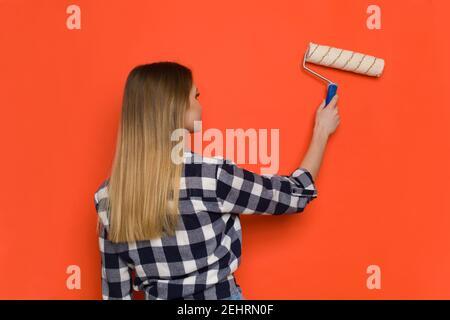 Jeune femme Blonde dans le maillot Lumberjack est peinture mur d'orange avec rouleau de peinture. Vue arrière. Prise de vue à la taille.