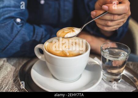 Cappuccino, femme buvant du café au café. Vue rapprochée de la cuillère dans la main féminine et de la tasse de café blanc
