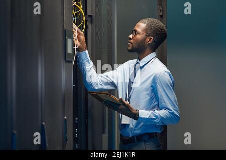 Portrait graphique de l'ingénieur réseau afro-américain qui connecte les câbles dans l'armoire de serveur tout en travaillant avec le supercalculateur dans le centre de données, c