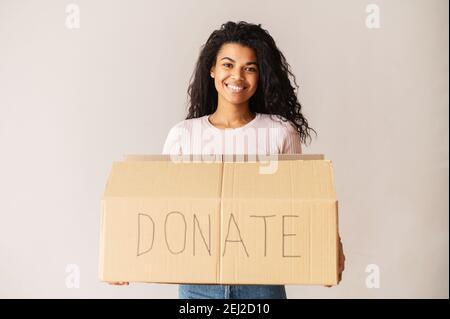 Gentille volontaire afro-américaine souriante avec des cheveux fclés et foncés tenant une boîte en carton, en faisant don de ses choses à la charité, pour les orphelins et les sans-abri