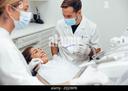 Femme souriant pendant son traitement dentaire chez le dentiste. Médecins dentaires traitant une patiente à l'hôpital.