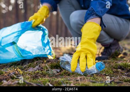 Pollution de l'environnement. Cueillir volontairement une bouteille en plastique dans une forêt sale. Nettoyez la Terre ! Gros plan sur la main avec un gant de protection jaune Banque D'Images