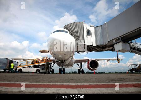 Embarquement des passagers à bord de l'avion par la passerelle d'embarquement. L'avion atterrit à l'aéroport international. Chargement des bagages. Avion blanc. Borne Banque D'Images