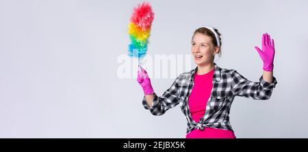 Bannière : format long sur fond gris. Surprise jeune femme dans des gants roses tenant la brosse à poussière avec les mains vers le haut, regardant côté avec l'émotion choquée sur