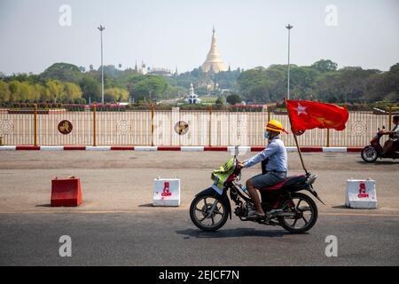 Yangon, Myanmar. 22 février 2021. Un manifestant passe devant le parc du peuple en conduisant une moto avec un drapeau de la Ligue nationale pour la démocratie (NLD) lors de la manifestation contre la junte à Yangon le 22 février 2021. Des milliers de personnes ont envahi les rues de Yangon le 22e jour de la manifestation contre un coup d'État militaire et ont demandé la libération d'Aung San Suu Kyi. Crédit : ZUMA Press, Inc./Alay Live News