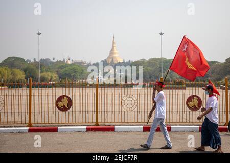 Yangon, Myanmar. 22 février 2021. Un manifestant passe devant le parc du peuple tout en tenant un drapeau de la Ligue nationale pour la démocratie (NLD) lors de la manifestation contre la junte à Yangon le 22 février 2021. Des milliers de personnes ont envahi les rues de Yangon le 22e jour de la manifestation contre un coup d'État militaire et ont demandé la libération d'Aung San Suu Kyi. Crédit : ZUMA Press, Inc./Alay Live News