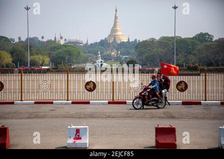 Yangon, Myanmar. 22 février 2021. Les manifestants passent devant le parc du peuple en conduisant une moto avec un drapeau de la Ligue nationale pour la démocratie (NLD) lors de la manifestation contre la junte à Yangon le 22 février 2021. Des milliers de personnes ont envahi les rues de Yangon le 22e jour de la manifestation contre un coup d'État militaire et ont demandé la libération d'Aung San Suu Kyi. Crédit : ZUMA Press, Inc./Alay Live News