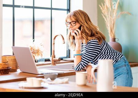 Photo d'une femme d'âge moyen utilisant un ordinateur portable et un téléphone portable dans la cuisine à la maison. Bureau à domicile.