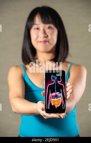 Femme tenant l'écran avec dessin du système digestif