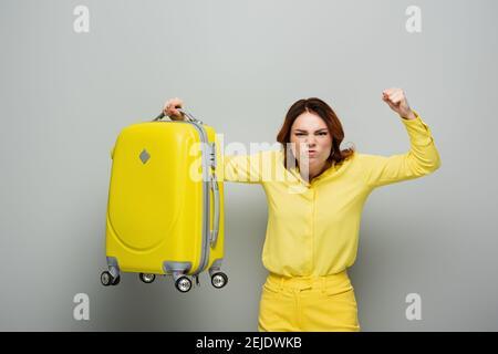 une femme en colère montrant le poing serré tout en tenant une valise jaune gris