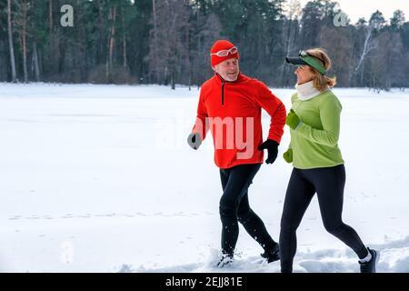 Couple senior souriant qui fait du jogging dans un parc hivernal enneigé.