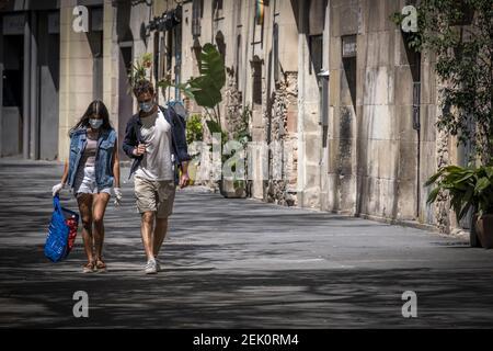 Un couple portant des masques pour le visage comme mesure préventive rentrent à la maison après avoir fait du shopping dans le cadre de la pandémie Covid-19. Barcelone fait face au 42e jour de confinement et de distance sociale. Seuls les établissements autorisés sont ouverts au public. Les rues restent vides sans piétons ni véhicules. (Photo par Paco Freire / SOPA Images / Sipa USA)