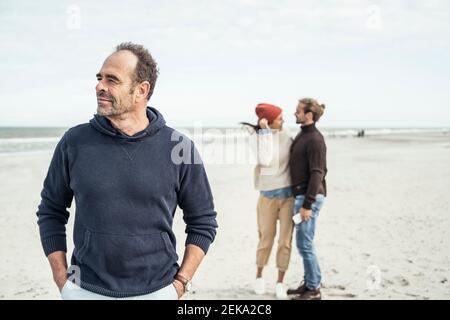 Portrait d'un homme debout sur une plage de sable avec un jeune couple en arrière-plan