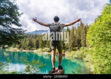 Homme insouciant portant un sac à dos debout avec des bras tendus contre le lac de Cauma à Graubunden Canton, Suisse