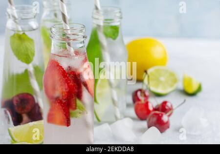 Beaucoup de bouteilles avec limonade d'été rafraîchissante avec citron vert, fraise, cerise, concombre et glace sur fond de béton gris