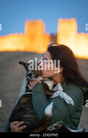 Femme caucasienne embrassant mignon chien brun avec un château plein de lumières dans le fond à Arraiolos, Alentejo Banque D'Images