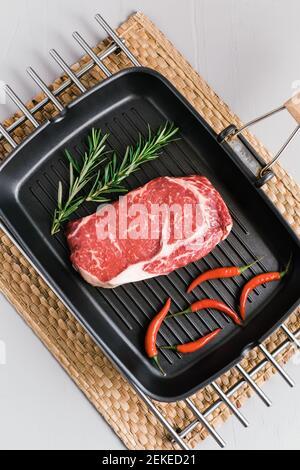 Steak de bœuf cru aux yeux sur une poêle noire avec piment et romarin, vue du dessus.
