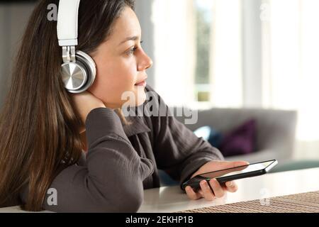 Femme pensive portant un casque sans fil qui envisage d'écouter de la musique à accueil