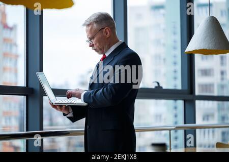 Sourire heureux directeur général pense à son développement de carrière réussi tout en se tenant debout avec un ordinateur portable dans son bureau près de l'arrière-plan d'une victoire