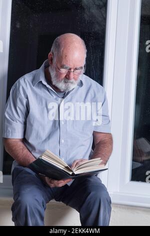 Homme âgé assis dans sa véranda la nuit pour lire un roman.