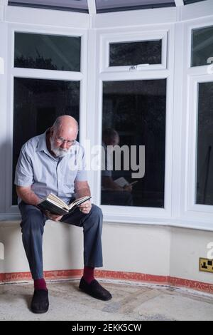 Homme âgé assis dans son jardin d'hiver lors d'une nuit de pluie lisant un roman.