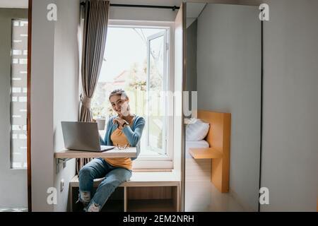 Une jeune femme confiante dans une tenue élégante et décontractée travaillant sur un ordinateur portable assis près de la fenêtre à la maison