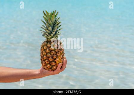 L'homme tient l'ananas sur fond de mer. Concept vacances et voyages. Banque D'Images