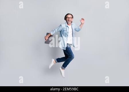 Vue sur toute la longueur de la taille du corps de l'homme magnifique et gai étonné ordinateur portable de transport jumping isolé sur fond gris pastel