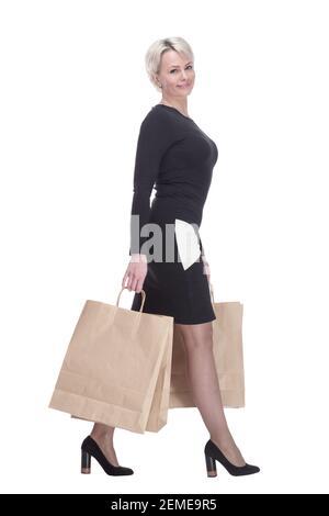 femme élégante souriante avec des sacs de shopping en avant.