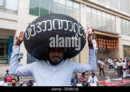 Yangon, Myanmar. 22 février 2021. Un manifestant anti-coup d'État militaire tenant un gros pneu sur la tête avec le mot « nous ne voulons pas de dictateur militaire » se tient tout en faisant le salut des trois doigts lors d'une manifestation. Une foule massive s'est emmenée dans les rues de Yangon pour protester contre le coup d'État militaire et a demandé la libération d'Aung San Suu Kyi. L'armée du Myanmar a arrêté le conseiller d'État du Myanmar Aung San Suu Kyi le 01 février 2021 et a déclaré l'état d'urgence tout en prenant le pouvoir dans le pays pendant un an après avoir perdu les élections contre la Ligue nationale pour la démocratie (crédit