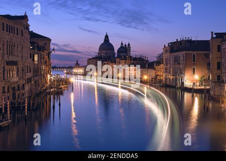 Venise la nuit. Image de paysage urbain du Grand Canal de Venise, avec la basilique Santa Maria della Salute reflétée dans la mer calme. Voyants du bateau passager allumés