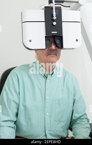 Patient mâle senior regardant à travers la lentille de l'équipement ophtalmologique pendant faire vérifier sa vue dans les cliniques contemporaines